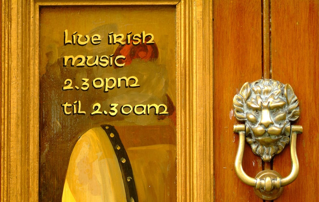 Close up of Dublin pub door with lion doorknob and live music sign